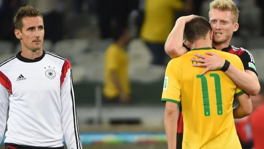 Germany's forward Andre Schuerrle (R) conforts Brazil's midfielder Oscar after the semi-final football match between Brazil and Germany at The Mineirao Stadium in Belo Horizonte during the 2014 FIFA World Cup on July 8, 2014.   AFP PHOTO / PEDRO UGARTE        (Photo credit should read PEDRO UGARTE/AFP/Getty Images)