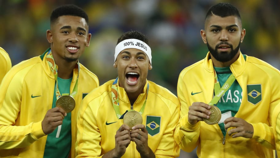 Brazil's players including Neymar (C) celebrate on the podium during the medal presentation following the Rio 2016 Olympic Games men's football gold medal match between Brazil and Germany at the Maracana stadium in Rio de Janeiro on August 20, 2016.  / AFP PHOTO / Odd Andersen        (Photo credit should read ODD ANDERSEN/AFP/Getty Images)