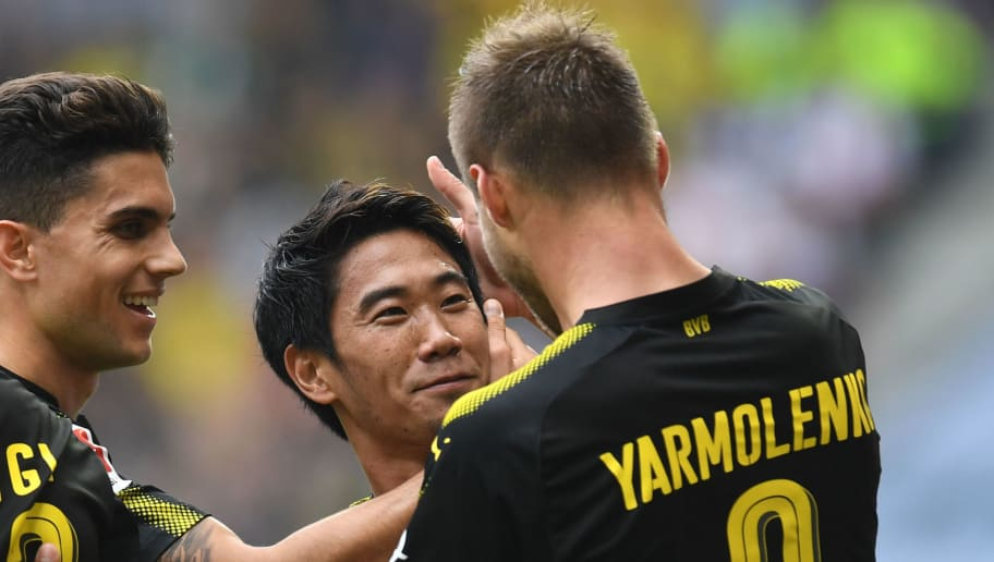 (L-R) Dortmund's Spanish defender Marc Barta, Dortmund's Japanese Shinji Kagawa and Dortmund's Ukrainian striker Andrey Yarmolenko celebrate scoring during the German first division Bundesliga football match between FC Augsburg and Borussia Dortmund in Augsburg, southern Germany on September 30, 2017. / AFP PHOTO / Christof STACHE / RESTRICTIONS: DURING MATCH TIME: DFL RULES TO LIMIT THE ONLINE USAGE TO 15 PICTURES PER MATCH AND FORBID IMAGE SEQUENCES TO SIMULATE VIDEO. == RESTRICTED TO EDITORIAL USE == FOR FURTHER QUERIES PLEASE CONTACT DFL DIRECTLY AT + 49 69 650050  / RESTRICTIONS: DURING MATCH TIME: DFL RULES TO LIMIT THE ONLINE USAGE TO 15 PICTURES PER MATCH AND FORBID IMAGE SEQUENCES TO SIMULATE VIDEO. == RESTRICTED TO EDITORIAL USE == FOR FURTHER QUERIES PLEASE CONTACT DFL DIRECTLY AT + 49 69 650050        (Photo credit should read CHRISTOF STACHE/AFP/Getty Images)