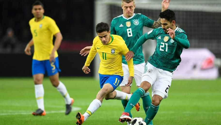 Germany's midfielder Ilkay Gundogan (R) and Germany's midfielder Toni Kroos (C) vie for the ball with Brazil's midfielder Philippe Coutinho during the international friendly football match between Germany and Brazil in Berlin, on March 27, 2018. / AFP PHOTO / ROBERT MICHAEL        (Photo credit should read ROBERT MICHAEL/AFP/Getty Images)