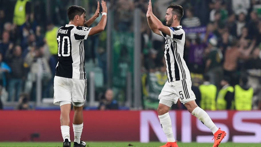 Juventus midfielder Miralem Pjanic (R) celebrates with Juventus' forward from Argentina Paulo Dybala after scoring during the UEFA Champions League Group D football match Juventus vs Sporting CP at the Juventus stadium on October 17, 2017 in Turin.  / AFP PHOTO / Miguel MEDINA        (Photo credit should read MIGUEL MEDINA/AFP/Getty Images)