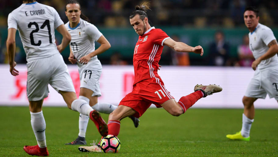 Gareth Bale of Wales (C) kicks the ball during the China Cup International Football Championship final between Wales and Uruguay in Nanning in China's southern Guangxi region on March 26, 2018. / AFP PHOTO / - / China OUT        (Photo credit should read -/AFP/Getty Images)