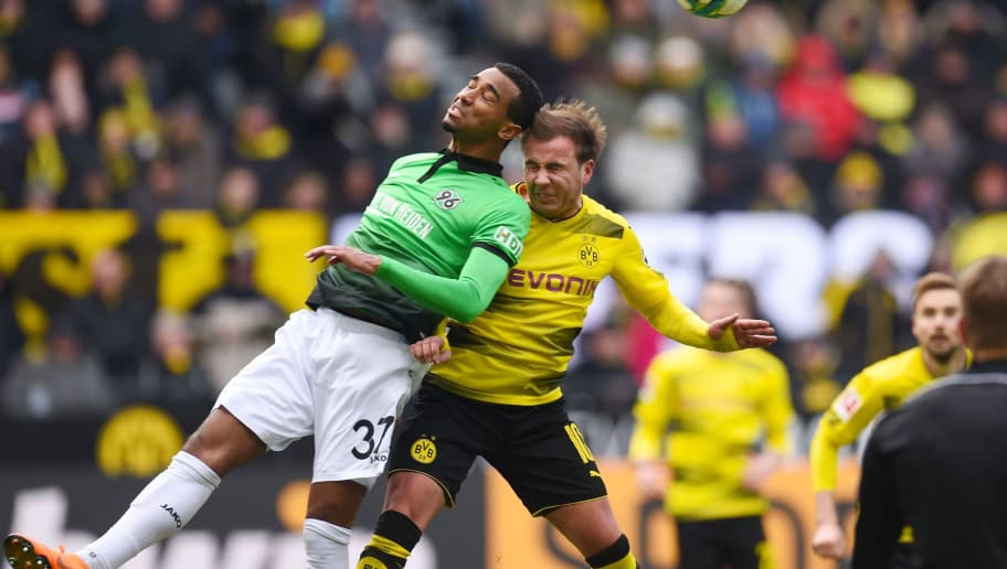 Dortmund's German midfielder Mario Goetze (R) and Hanover's Nigerian midfielder Noah Joel Sarenren Bazee vie for the ball during the German first division Bundesliga football match Borussia Dortmund vs Hanover 96, in Dortmund, western Germany, on March 18, 2018. / AFP PHOTO / Patrik STOLLARZ / RESTRICTIONS: DURING MATCH TIME: DFL RULES TO LIMIT THE ONLINE USAGE TO 15 PICTURES PER MATCH AND FORBID IMAGE SEQUENCES TO SIMULATE VIDEO. == RESTRICTED TO EDITORIAL USE == FOR FURTHER QUERIES PLEASE CONTACT DFL DIRECTLY AT + 49 69 650050         (Photo credit should read PATRIK STOLLARZ/AFP/Getty Images)
