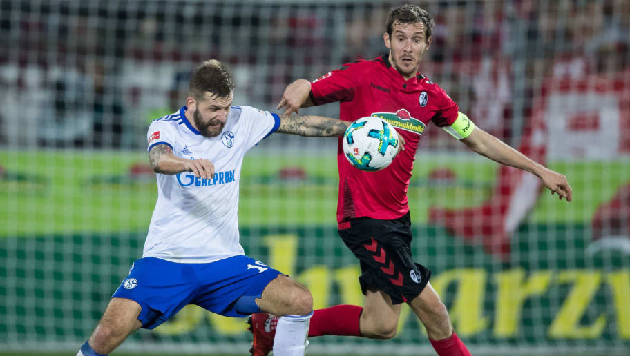FREIBURG IM BREISGAU, GERMANY - NOVEMBER 04: Guido Burgstaller of Schalke is challenged by Julian Schuster of Freiburg during the Bundesliga match between Sport-Club Freiburg and FC Schalke 04 at Schwarzwald-Stadion on November 4, 2017 in Freiburg im Breisgau, Germany. (Photo by Simon Hofmann/Bongarts/Getty Images)