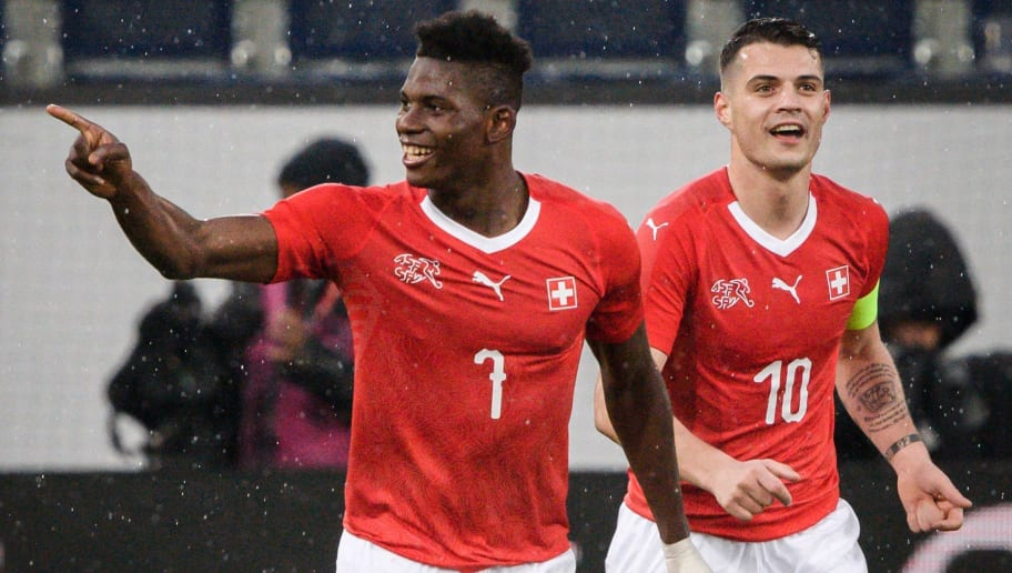 Switzerland's forward Breel Embolo (L) reacts next toteammates midfielder Granit Xhaka after scoring a goal during the international friendly football match between Switzerland and Panama in Lucerne on March 27, 2018. / AFP PHOTO / Fabrice COFFRINI        (Photo credit should read FABRICE COFFRINI/AFP/Getty Images)
