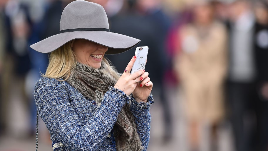 A racegoer checks her phone on the final day of the Cheltenham Festival horse racing meet at Cheltenham Racecourse in Gloucestershire, south-west England, on March 16, 2018.  / AFP PHOTO / GLYN KIRK        (Photo credit should read GLYN KIRK/AFP/Getty Images)
