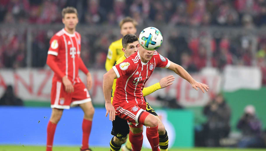 MUNICH, GERMANY - DECEMBER 20: Joshua Kimmich of Bayern Muenchen and Christian Pulisic of Borussia Dortmund eye the ball during the DFB Cup match between Bayern Muenchen and Borussia Dortmund at Allianz Arena on December 20, 2017 in Munich, Germany. (Photo by Sebastian Widmann/Bongarts/Getty Images)