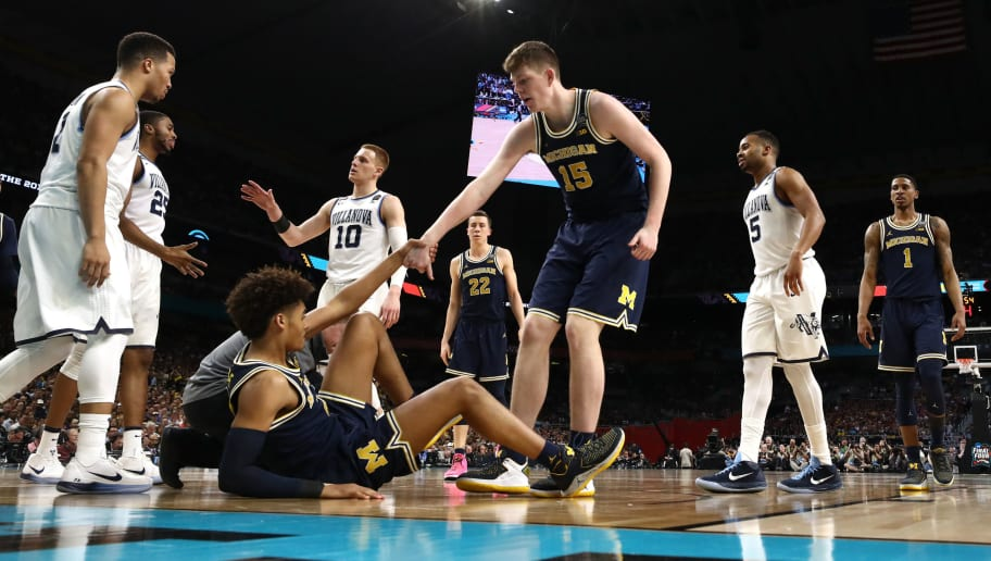 SAN ANTONIO, TX - APRIL 02: Jordan Poole #2 of the Michigan Wolverines is helped to his feat by teammate Jon Teske #15 against the Villanova Wildcats in the second half during the 2018 NCAA Men's Final Four National Championship game at the Alamodome on April 2, 2018 in San Antonio, Texas.  (Photo by Tom Pennington/Getty Images)