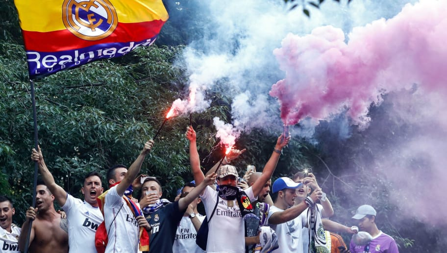 Real Madrid football team fans light flares as they celebrate their team's opening goal in the surroundings of the Santiago Bernabeu stadium in Madrid on June 3, 2017 during the UEFA Champions League football match final Juventus vs Real Madrid CF held at the National Stadium of Wales in Cardiff. / AFP PHOTO / OSCAR DEL POZO        (Photo credit should read OSCAR DEL POZO/AFP/Getty Images)