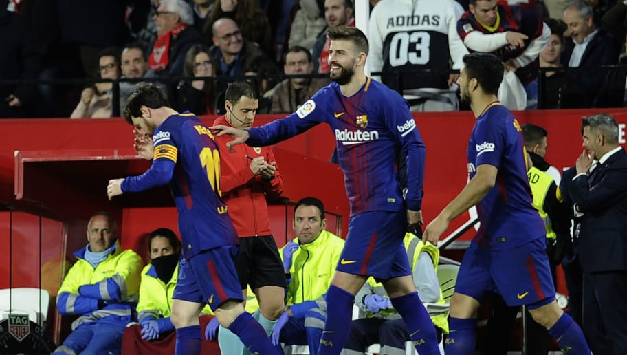 Barcelona's Argentinian forward Lionel Messi (L) celebrates a goal with Barcelona's Spanish defender Gerard Pique (C) and Barcelona's Uruguayan forward Luis Suarez during the Spanish League football match between Sevilla FC and FC Barcelona at the Ramon Sanchez Pizjuan stadium on March 31, 2018. / AFP PHOTO / Cristina Quicler        (Photo credit should read CRISTINA QUICLER/AFP/Getty Images)