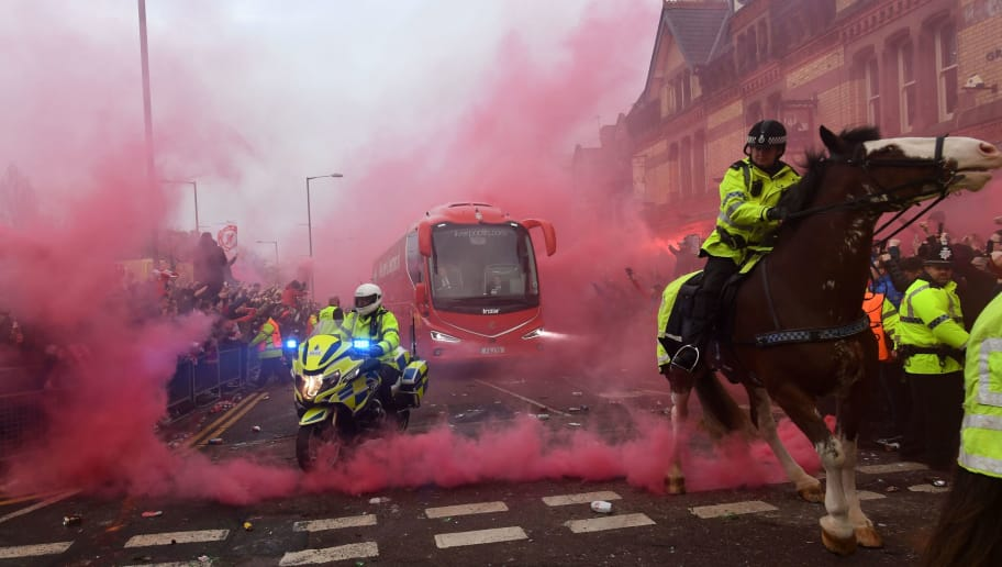 TOPSHOT - Police keep control as Liverpool players arrive by bus through smoke and beercans before the UEFA Champions League first leg quarter-final football match between Liverpool and Manchester City, at Anfield stadium in Liverpool, north west England on April 4, 2018. / AFP PHOTO / Paul ELLIS        (Photo credit should read PAUL ELLIS/AFP/Getty Images)