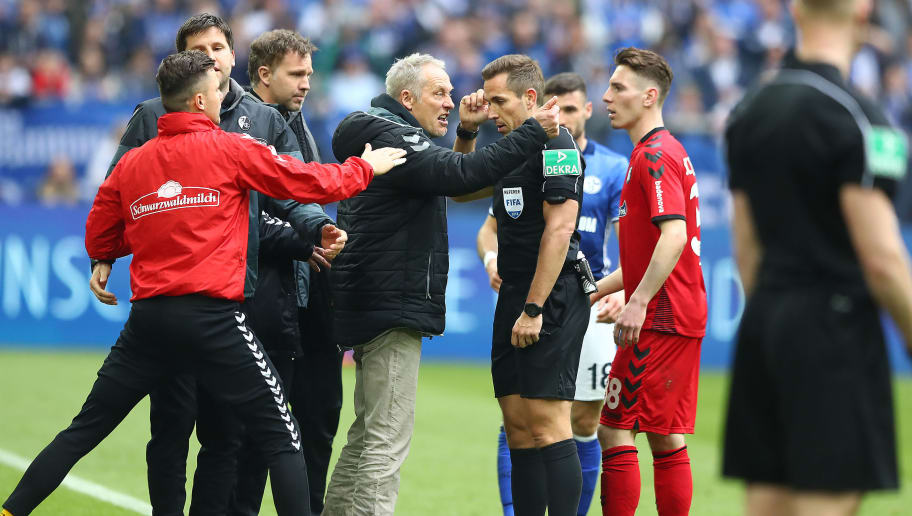 GELSENKIRCHEN, GERMANY - MARCH 31: Coach Christian Streich of Freiburg (c) argues with referee Tobias Stieler after Nils Petersen of Freiburg (not seen) was sent of with a red card, during the Bundesliga match between FC Schalke 04 and Sport-Club Freiburg at Veltins-Arena on March 31, 2018 in Gelsenkirchen, Germany. (Photo by Martin Rose/Bongarts/Getty Images)