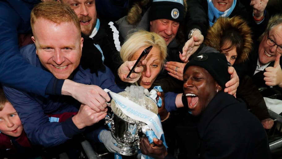 Manchester City's French defender Benjamin Mendy shows fans the trophy as Manchester city players celebrate their victory in the English League Cup final football match between Manchester City and Arsenal at Wembley stadium in north London on February 25, 2018. Manchester City won the first trophy of the Guardiola era on Sunday, thumping a disappointing Arsenal 3-0 in the League Cup final at Wembley. / AFP PHOTO / Adrian DENNIS / RESTRICTED TO EDITORIAL USE. No use with unauthorized audio, video, data, fixture lists, club/league logos or 'live' services. Online in-match use limited to 75 images, no video emulation. No use in betting, games or single club/league/player publications.  /         (Photo credit should read ADRIAN DENNIS/AFP/Getty Images)