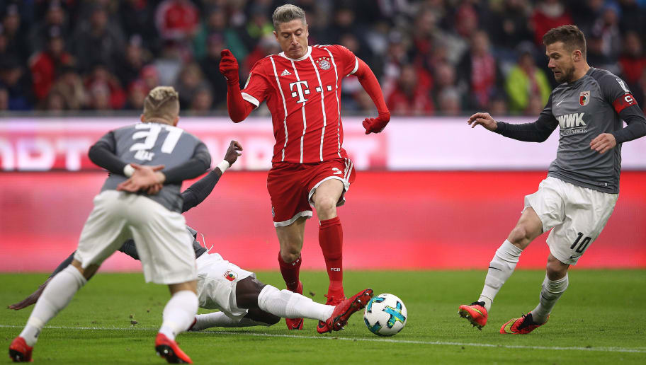 MUNICH, GERMANY - NOVEMBER 18: Robert Lewandowski of Bayern Muenchen (c) fights for the ball with Kevin Danso of Augsburg (covered) during the Bundesliga match between FC Bayern Muenchen and FC Augsburg at Allianz Arena on November 18, 2017 in Munich, Germany. (Photo by Adam Pretty/Bongarts/Getty Images)