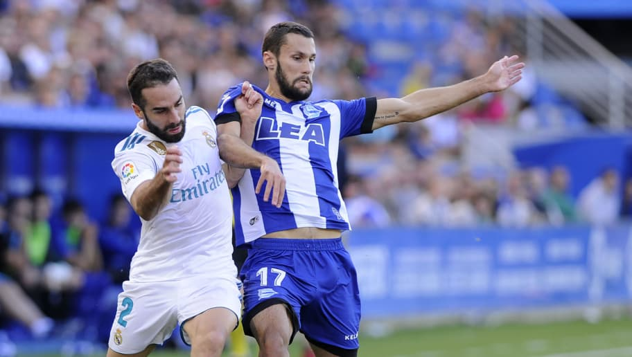Real Madrid's defender from Spain Daniel Carvajal (L) vies with Alaves' forward from Spain Alfonso Pedraza during the Spanish league football match Deportivo Alaves vs Real Madrid CF at the Mendizorroza stadium in Vitoria on September 23, 2017.  / AFP PHOTO / ANDER GILLENEA        (Photo credit should read ANDER GILLENEA/AFP/Getty Images)