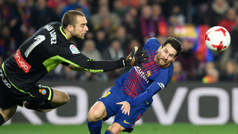 Espanyol's Spanish goalkeeper Pau Lopez (L) tries to block a shot on goal by Barcelona's Argentinian forward Lionel Messi during the Spanish 'Copa del Rey' (King's cup) quarter-final second leg football match between FC Barcelona and RCD Espanyol at the Camp Nou stadium in Barcelona on January 25, 2018.  / AFP PHOTO / LLUIS GENE        (Photo credit should read LLUIS GENE/AFP/Getty Images)
