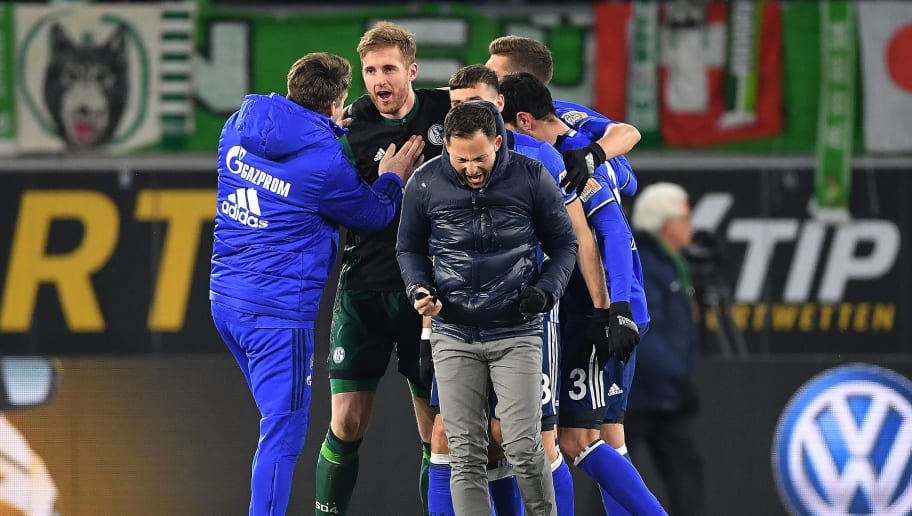 WOLFSBURG, GERMANY - MARCH 17: Goalkeeper Ralf Faehrmann of Schalke is celebrated by players of officials of Schalke, while coach Domenico Tedesco of Schalke reacts, after the Bundesliga match between VfL Wolfsburg and FC Schalke 04 at Volkswagen Arena on March 17, 2018 in Wolfsburg, Germany. (Photo by Stuart Franklin/Bongarts/Getty Images)