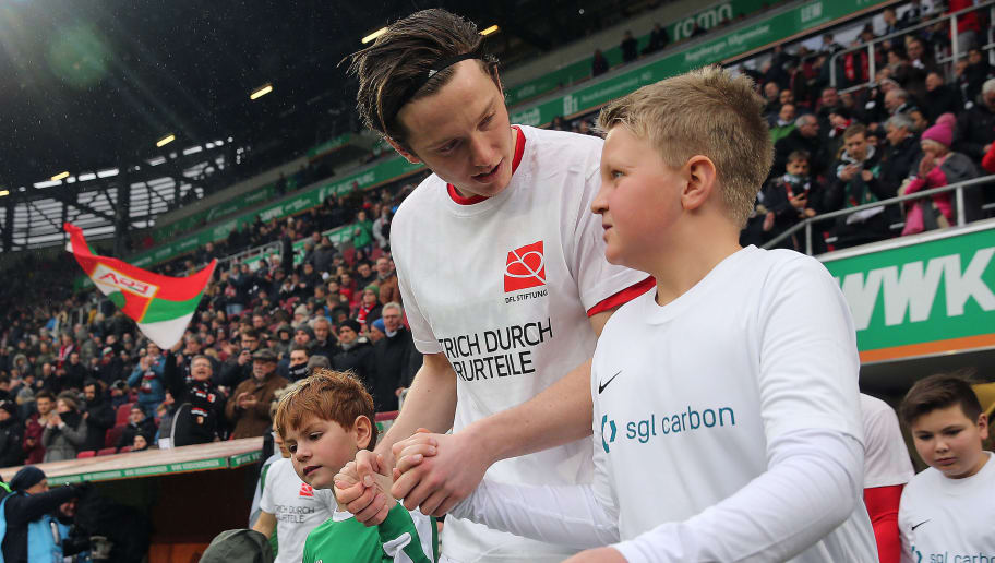 AUGSBURG, GERMANY - MARCH 17: Michael Gregoritsch of Augsburg walks on the pitch with a mascot and a shirt  against discrimination for the campaign 'Say No to prejudice', an anti-discrimination campaign, before the Bundesliga match between FC Augsburg and SV Werder Bremen at WWK-Arena on March 17, 2018 in Augsburg, Germany. (Photo by Alex Grimm/Bongarts/Getty Images)
