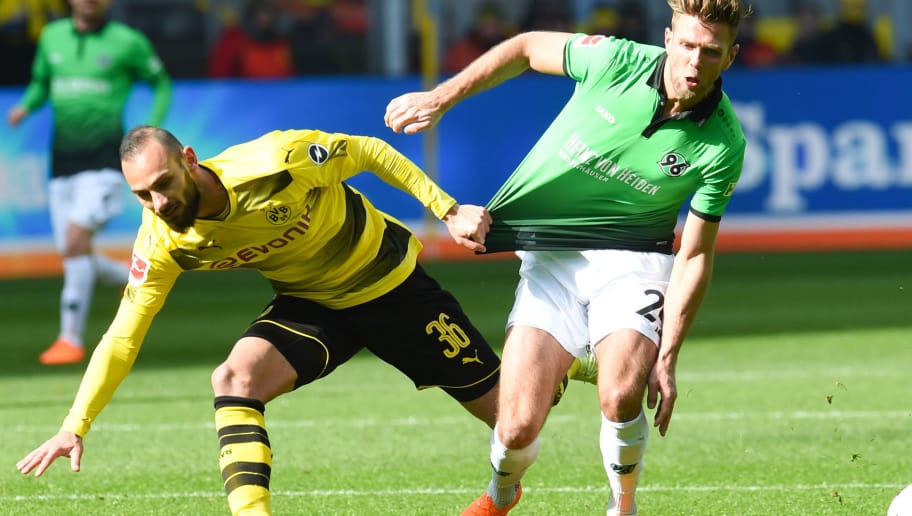 Hanover's German defender Oliver Sorg (R) and Dortmund's Turkish defender Omer Toprak vie for the ball during the German first division Bundesliga football match Borussia Dortmund vs Hannover 96 in Dortmund, western Germany, on March 18, 2018. / AFP PHOTO / PATRIK STOLLARZ / RESTRICTIONS: DURING MATCH TIME: DFL RULES TO LIMIT THE ONLINE USAGE TO 15 PICTURES PER MATCH AND FORBID IMAGE SEQUENCES TO SIMULATE VIDEO. == RESTRICTED TO EDITORIAL USE == FOR FURTHER QUERIES PLEASE CONTACT DFL DIRECTLY AT + 49 69 650050         (Photo credit should read PATRIK STOLLARZ/AFP/Getty Images)