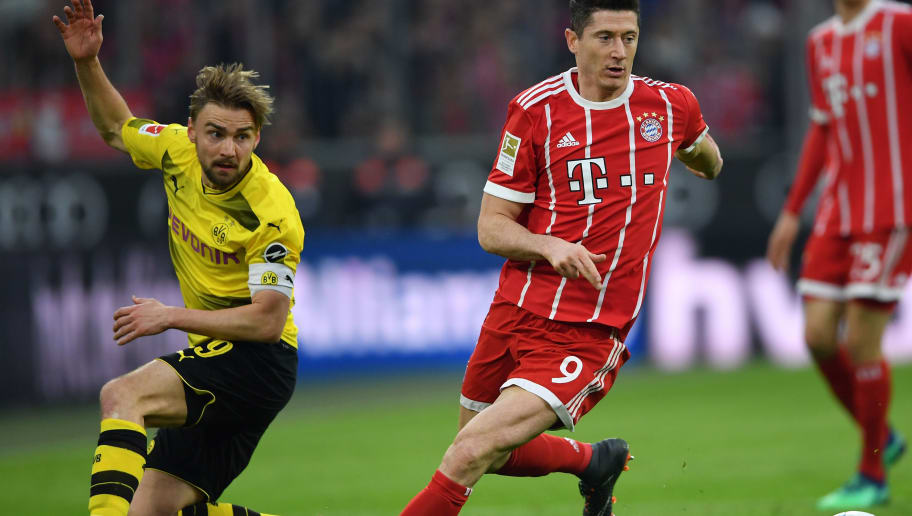 MUNICH, GERMANY - MARCH 31:  Robert Lewandowski of Bayern is challenged by Marcel Schmelzer of Dortmund during the Bundesliga match between FC Bayern Muenchen and Borussia Dortmund at Allianz Arena on March 31, 2018 in Munich, Germany.  (Photo by Stuart Franklin/Bongarts/Getty Images)