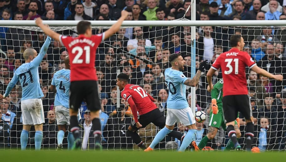 Manchester United's English defender Chris Smalling (C) celebrates scoring his team's third goal during the English Premier League football match between Manchester City and Manchester United at the Etihad Stadium in Manchester, north west England, on April 7, 2018. / AFP PHOTO / Paul ELLIS / RESTRICTED TO EDITORIAL USE. No use with unauthorized audio, video, data, fixture lists, club/league logos or 'live' services. Online in-match use limited to 75 images, no video emulation. No use in betting, games or single club/league/player publications.  /         (Photo credit should read PAUL ELLIS/AFP/Getty Images)