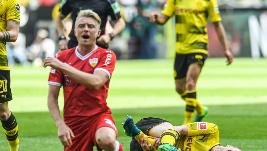 Dortmund's German forward Marco Reus and Stuttgart's German defender Andreas Beck vie for the ball during the German first division Bundesliga football match Borussia Dortmund vs VfB Stuttgart, in Dortmund, western Germany, on April 8, 2018. / AFP PHOTO / Patrik STOLLARZ / RESTRICTIONS: DURING MATCH TIME: DFL RULES TO LIMIT THE ONLINE USAGE TO 15 PICTURES PER MATCH AND FORBID IMAGE SEQUENCES TO SIMULATE VIDEO. == RESTRICTED TO EDITORIAL USE == FOR FURTHER QUERIES PLEASE CONTACT DFL DIRECTLY AT + 49 69 650050         (Photo credit should read PATRIK STOLLARZ/AFP/Getty Images)