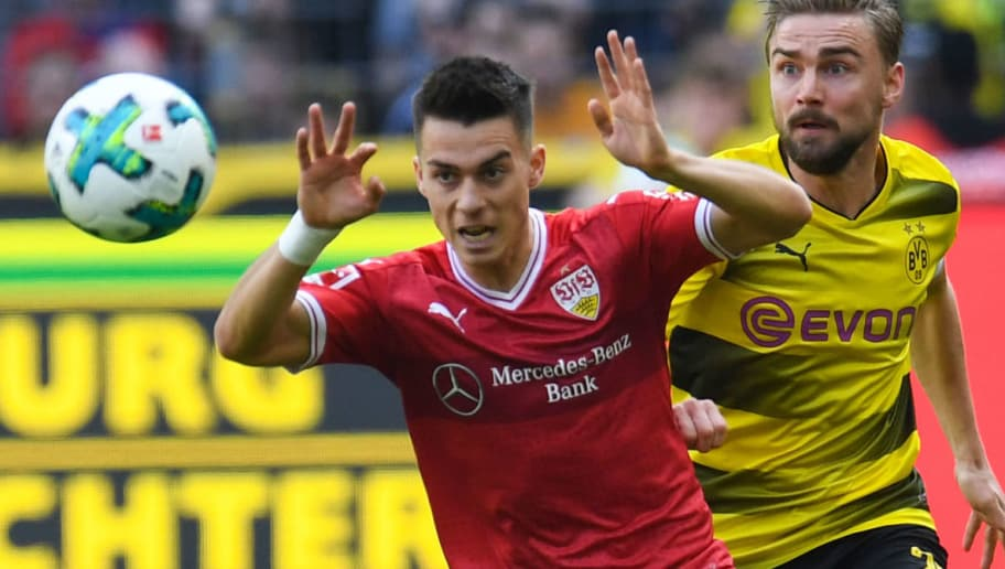 Dortmund's German defender Marcel Schmelzer and Stuttgart's German midfielder Erik Thommy vie for the ball during the German first division Bundesliga football match Borussia Dortmund vs VfB Stuttgart, in Dortmund, western Germany, on April 8, 2018. / AFP PHOTO / Patrik STOLLARZ / RESTRICTIONS: DURING MATCH TIME: DFL RULES TO LIMIT THE ONLINE USAGE TO 15 PICTURES PER MATCH AND FORBID IMAGE SEQUENCES TO SIMULATE VIDEO. == RESTRICTED TO EDITORIAL USE == FOR FURTHER QUERIES PLEASE CONTACT DFL DIRECTLY AT + 49 69 650050         (Photo credit should read PATRIK STOLLARZ/AFP/Getty Images)