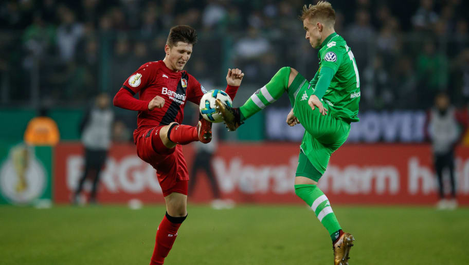 MOENCHENGLADBACH, GERMANY - DECEMBER 20: Panagiotis Retsos of Leverkusen challenges Oscar Wendt of Moenchengladbach during the DFB Cup match between Borussia Moenchengladbach and Bayer Leverkusen at Borussia-Park on December 20, 2017 in Moenchengladbach, Germany.  (Photo by Lars Baron/Bongarts/Getty Images)