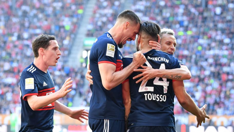 AUGSBURG, GERMANY - APRIL 07: Sebastian Rudy (l-r), Sandro Wagner and Rafinha celebrate with Corentin Tolisso  of Bayern Muenchen after he scored their teams first goal during the Bundesliga match between FC Augsburg and FC Bayern Muenchen at WWK-Arena on April 7, 2018 in Augsburg, Germany. (Photo by Sebastian Widmann/Bongarts/Getty Images)