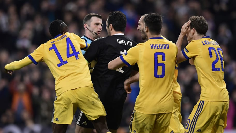 TOPSHOT - Juventus' Italian goalkeeper Gianluigi Buffon (3L) argues with British referee Michael Oliver during the UEFA Champions League quarter-final second leg football match between Real Madrid CF and Juventus FC at the Santiago Bernabeu stadium in Madrid on April 11, 2018. / AFP PHOTO / JAVIER SORIANO        (Photo credit should read JAVIER SORIANO/AFP/Getty Images)