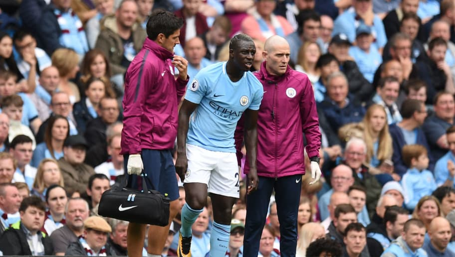 Manchester City's French defender Benjamin Mendy (C) is helped by medics during the English Premier League football match between Manchester City and Crystal Palace at the Etihad Stadium in Manchester, north west England, on September 23, 2017. / AFP PHOTO / Oli SCARFF / RESTRICTED TO EDITORIAL USE. No use with unauthorized audio, video, data, fixture lists, club/league logos or 'live' services. Online in-match use limited to 75 images, no video emulation. No use in betting, games or single club/league/player publications.  /         (Photo credit should read OLI SCARFF/AFP/Getty Images)