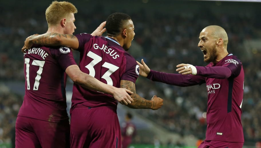 Manchester City's Brazilian striker Gabriel Jesus (C) celebrates with Manchester City's Belgian midfielder Kevin De Bruyne (L) and Manchester City's Spanish midfielder David Silva (R) after scoring the opening goal of the English Premier League football match between Tottenham Hotspur and Manchester City at Wembley Stadium in London, on April 14, 2018. / AFP PHOTO / Ian KINGTON / RESTRICTED TO EDITORIAL USE. No use with unauthorized audio, video, data, fixture lists, club/league logos or 'live' services. Online in-match use limited to 75 images, no video emulation. No use in betting, games or single club/league/player publications.  /         (Photo credit should read IAN KINGTON/AFP/Getty Images)