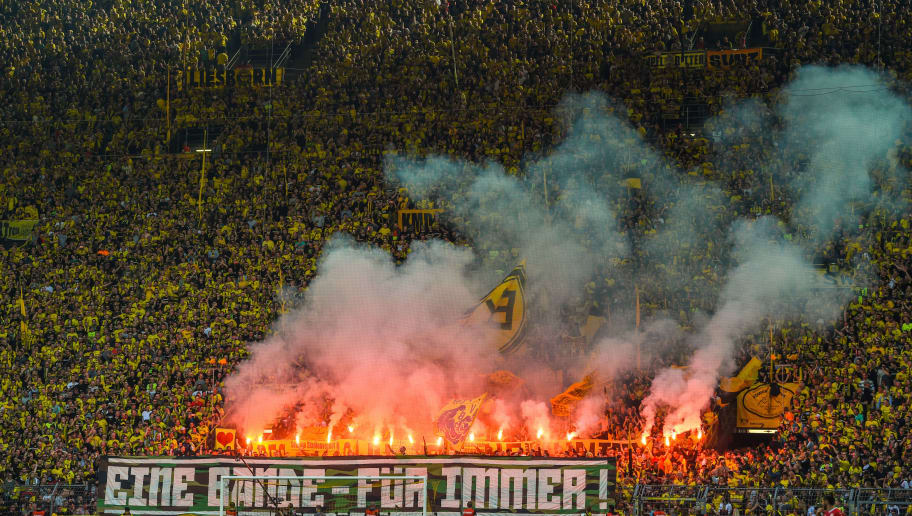 Dortmund fans light flares during the German first division Bundesliga football match Borussia Dortmund vs VfB Stuttgart, in Dortmund, western Germany, on April 8, 2018. / AFP PHOTO / Patrik STOLLARZ / RESTRICTIONS: DURING MATCH TIME: DFL RULES TO LIMIT THE ONLINE USAGE TO 15 PICTURES PER MATCH AND FORBID IMAGE SEQUENCES TO SIMULATE VIDEO. == RESTRICTED TO EDITORIAL USE == FOR FURTHER QUERIES PLEASE CONTACT DFL DIRECTLY AT + 49 69 650050         (Photo credit should read PATRIK STOLLARZ/AFP/Getty Images)