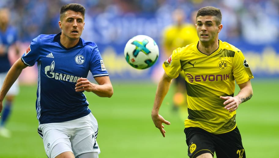 Schalke's Austrian midfielder Alessandro Schoepf (L) and Dortmund's US midfielder Christian Pulisic vie for the ball during the German first division Bundesliga football match of Schalke 04 vs Borussia Dortmund in Gelsenkirchen, western Germany, on April 15, 2018. / AFP PHOTO / Patrik STOLLARZ / RESTRICTIONS: DURING MATCH TIME: DFL RULES TO LIMIT THE ONLINE USAGE TO 15 PICTURES PER MATCH AND FORBID IMAGE SEQUENCES TO SIMULATE VIDEO. == RESTRICTED TO EDITORIAL USE == FOR FURTHER QUERIES PLEASE CONTACT DFL DIRECTLY AT + 49 69 650050         (Photo credit should read PATRIK STOLLARZ/AFP/Getty Images)