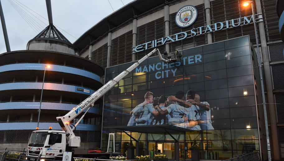 A workman prepares to change the external panel designs on the Etihad Stadium in Manchester, north west England, on April 15, 2018, to mark Manchester City's Premier League title win. Manchester City were crowned Premier League champions on Sunday as Manchester United crashed to a shock 1-0 defeat against West Bromwich Albion. / AFP PHOTO / Paul ELLIS        (Photo credit should read PAUL ELLIS/AFP/Getty Images)