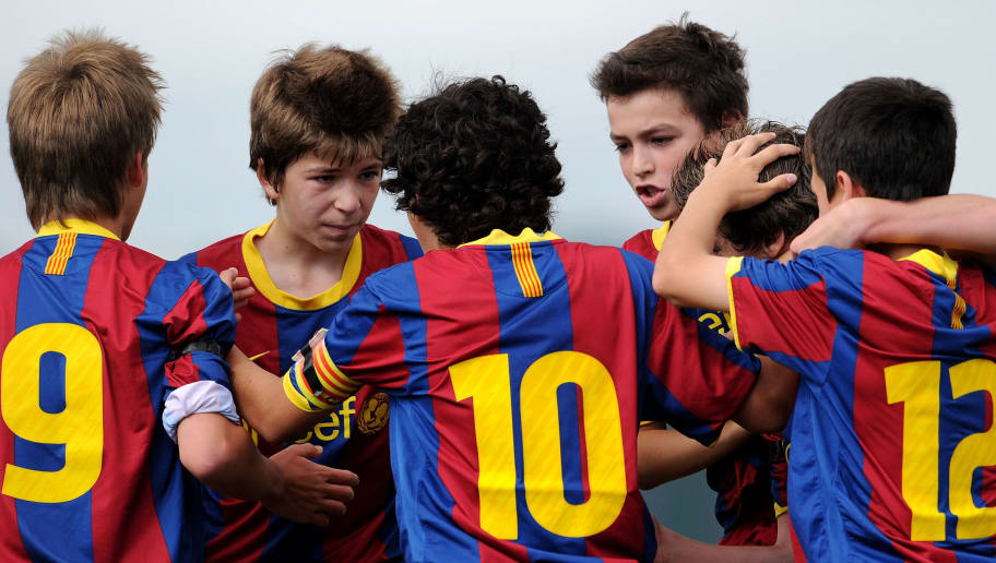 BARCELONA, SPAIN - MAY 15:  Barcelona youth players celebrate a goal during their match against Espanyol on one of the pitches at the Joan Camper training ground on May 15, 2011 in Barcelona, Spain. Every weekend various teams of Barcelona youth players play in matches with the hope of one day making it to the top.  (Photo by Jasper Juinen/Getty Images)
