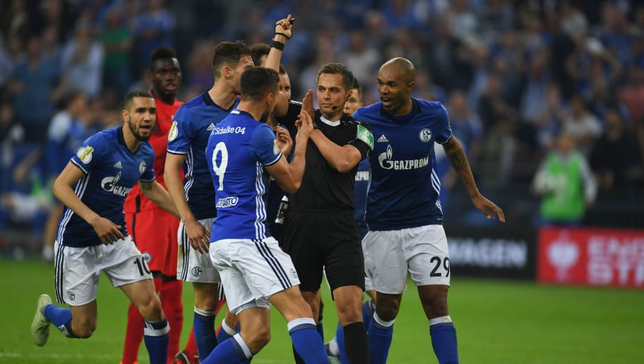 Schalke players arguee with referee Robert Hartmann during the German Cup DFB Pokal semi-final football match Schalke 04 vs Eintracht Frankfurt in Gelsenkirchen, western Germany, on April 18, 2018. / AFP PHOTO / Patrik STOLLARZ / RESTRICTIONS: ACCORDING TO DFB RULES IMAGE SEQUENCES TO SIMULATE VIDEO IS NOT ALLOWED DURING MATCH TIME. MOBILE (MMS) USE IS NOT ALLOWED DURING AND FOR FURTHER TWO HOURS AFTER THE MATCH. == RESTRICTED TO EDITORIAL USE == FOR MORE INFORMATION CONTACT DFB DIRECTLY AT +49 69 67880   /         (Photo credit should read PATRIK STOLLARZ/AFP/Getty Images)