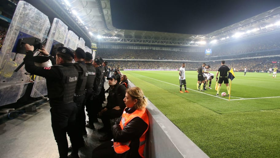 Besiktas Portuguese midfielder Ricardo Quaresma (4th R) prepares to kick a corner shot as Turkish anti riot police officers (L) hold their shields to protect players from objects potentially thrown from the tribunes, during the Ziraat Turkish Cup semi final second leg football match between Fenerbahce and Besiktas on April 19, 2018 at Fenerbahce stadium in Istanbul. - Besiktas head coach Senol Gunes was hospitalized on April 19 after being hit by a object on the head during the second half of a cup match against Fenerbahce's rival team, a spectacular incident that prompted the referee to suspend the match. (Photo by STRINGER / AFP)        (Photo credit should read STRINGER/AFP/Getty Images)