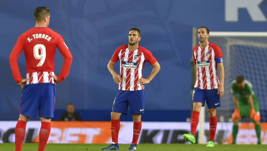 Atletico Madrid's Spanish forward Fernando Torres (L), Atletico Madrid's Spanish midfielder Koke (C) and Atletico Madrid's Uruguayan defender Diego Godin stand on the field after Real Sociedad's third goal during the Spanish league football match Real Sociedad vs Club Atletico de Madrid at the Anoeta stadium in San Sebastian on April 19, 2018. (Photo by ANDER GILLENEA / AFP)        (Photo credit should read ANDER GILLENEA/AFP/Getty Images)