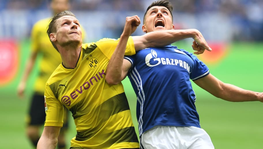 Dortmund's Polish defender Lukasz Piszczek (L) and Schalke's Austrian midfielder Alessandro Schoepf vie for the ball during the German first division Bundesliga football match of Schalke 04 vs Borussia Dortmund in Gelsenkirchen, western Germany, on April 15, 2018. / AFP PHOTO / Patrik STOLLARZ / RESTRICTIONS: DURING MATCH TIME: DFL RULES TO LIMIT THE ONLINE USAGE TO 15 PICTURES PER MATCH AND FORBID IMAGE SEQUENCES TO SIMULATE VIDEO. == RESTRICTED TO EDITORIAL USE == FOR FURTHER QUERIES PLEASE CONTACT DFL DIRECTLY AT + 49 69 650050         (Photo credit should read PATRIK STOLLARZ/AFP/Getty Images)