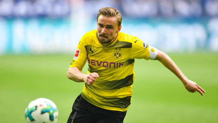 Dortmund's German defender Marcel Schmelzer vies for the ball during the German first division Bundesliga football match FC Schalke 04 vs Borussia Dortmund, in Gelsenkirchen, western Germany, on April 15, 2018. / AFP PHOTO / Patrik STOLLARZ / RESTRICTIONS: DURING MATCH TIME: DFL RULES TO LIMIT THE ONLINE USAGE TO 15 PICTURES PER MATCH AND FORBID IMAGE SEQUENCES TO SIMULATE VIDEO. == RESTRICTED TO EDITORIAL USE == FOR FURTHER QUERIES PLEASE CONTACT DFL DIRECTLY AT + 49 69 650050         (Photo credit should read PATRIK STOLLARZ/AFP/Getty Images)