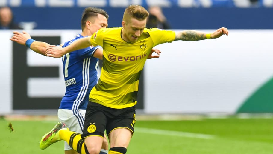 Schalke's Ukrainian midfielder Yevhen Konoplyanka (L) and Dortmund's German forward Marco Reus vie for the ball during the German first division Bundesliga football match of Schalke 04 vs Borussia Dortmund in Gelsenkirchen, western Germany, on April 15, 2018. / AFP PHOTO / Patrik STOLLARZ / RESTRICTIONS: DURING MATCH TIME: DFL RULES TO LIMIT THE ONLINE USAGE TO 15 PICTURES PER MATCH AND FORBID IMAGE SEQUENCES TO SIMULATE VIDEO. == RESTRICTED TO EDITORIAL USE == FOR FURTHER QUERIES PLEASE CONTACT DFL DIRECTLY AT + 49 69 650050         (Photo credit should read PATRIK STOLLARZ/AFP/Getty Images)