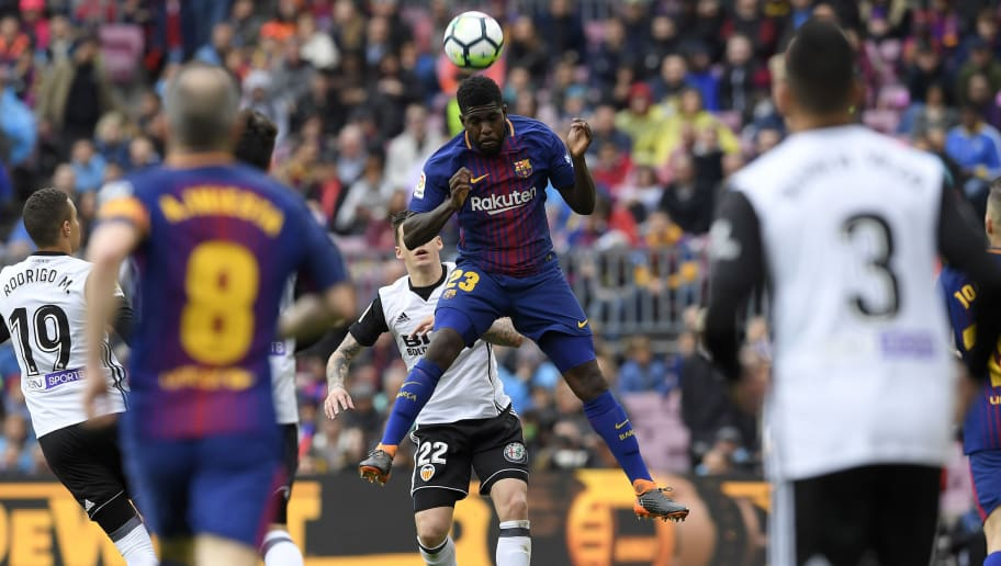 Barcelona's French defender Samuel Umtiti (TOP) heads the ball during the Spanish league footbal match between FC Barcelona and Valencia CF at the Camp Nou stadium in Barcelona on April 14, 2018. / AFP PHOTO / LLUIS GENE        (Photo credit should read LLUIS GENE/AFP/Getty Images)