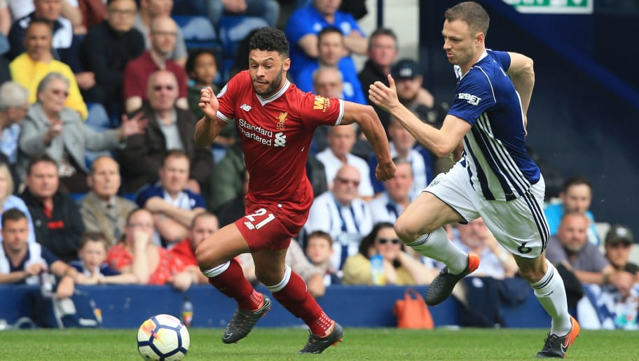 Liverpool's English midfielder Alex Oxlade-Chamberlain (L) takes on West Bromwich Albion's Northern Irish defender Jonny Evans (R) during the English Premier League football match between West Bromwich Albion and Liverpool at The Hawthorns stadium in West Bromwich, central England, on April 21, 2018. (Photo by Lindsey PARNABY / AFP) / RESTRICTED TO EDITORIAL USE. No use with unauthorized audio, video, data, fixture lists, club/league logos or 'live' services. Online in-match use limited to 75 images, no video emulation. No use in betting, games or single club/league/player publications. /         (Photo credit should read LINDSEY PARNABY/AFP/Getty Images)