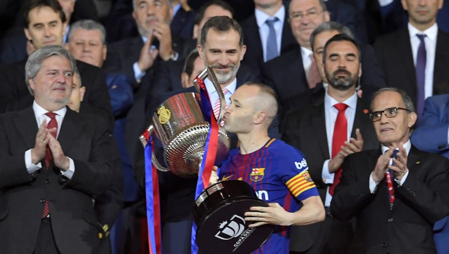 Spain's king Felipe VI looks at Barcelona's Spanish midfielder Andres Iniesta kissing the trophy after the Spanish Copa del Rey (King's Cup) final football match Sevilla FC against FC Barcelona at the Wanda Metropolitano stadium in Madrid on April 21, 2018. - Barcelona won 5-0. (Photo by LLUIS GENE / AFP)        (Photo credit should read LLUIS GENE/AFP/Getty Images)