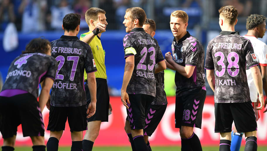 HAMBURG, GERMANY - APRIL 21: Players of Freiburg argue with referee Benjamin Cortus after he sent off Caglar Soeyuencue of Freiburg (l) with a red card, during the Bundesliga match between Hamburger SV and Sport-Club Freiburg at Volksparkstadion on April 21, 2018 in Hamburg, Germany. (Photo by Stuart Franklin/Bongarts/Getty Images)