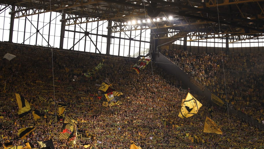 DORTMUND, GERMANY - APRIL 21: Fans of Dortmund  wave their flags at the 'Sudtribune' (South Stand) known as the Yellow Wall prior the Bundesliga match between Borussia Dortmund and Bayer 04 Leverkusen at Signal Iduna Park on April 21, 2018 in Dortmund, Germany. (Photo by Maja Hitij/Bongarts/Getty Images)