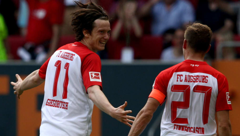 AUGSBURG, GERMANY - APRIL 22:  Michael Gregoritsch (L) of Augsburg celebrate with team mate Alfred Finnbogason after he scores the opening goal during the Bundesliga match between FC Augsburg and 1. FSV Mainz 05 at WWK-Arena on April 22, 2018 in Augsburg, Germany.  (Photo by Adam Pretty/Bongarts/Getty Images)