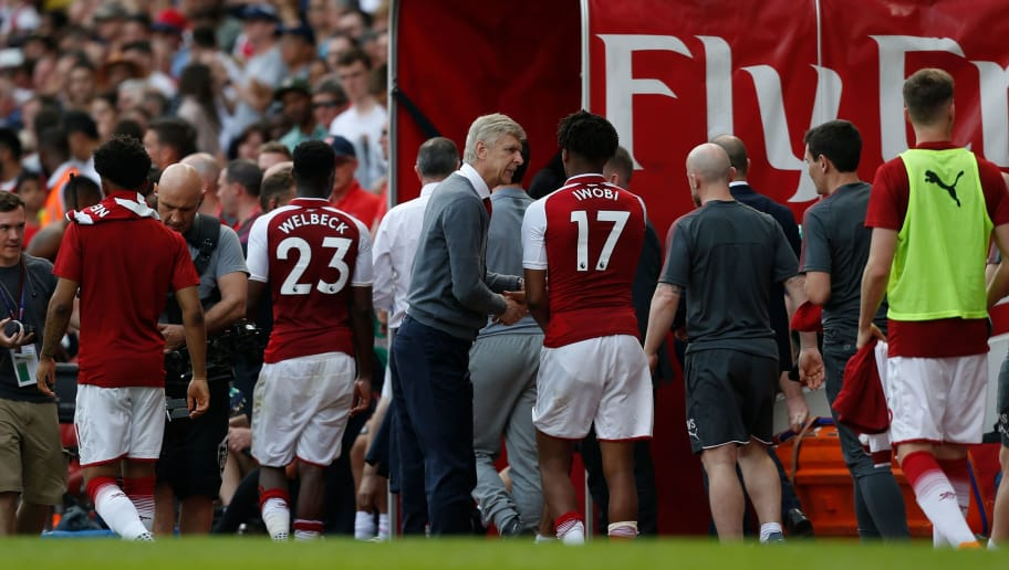 Arsenal's French manager Arsene Wenger (C) greets staff at the mouth of the player's tunnel at the end of the English Premier League football match between Arsenal and West Ham United at the Emirates Stadium in London on April 22, 2018. (Photo by Ian KINGTON / AFP) / RESTRICTED TO EDITORIAL USE. No use with unauthorized audio, video, data, fixture lists, club/league logos or 'live' services. Online in-match use limited to 75 images, no video emulation. No use in betting, games or single club/league/player publications. /         (Photo credit should read IAN KINGTON/AFP/Getty Images)