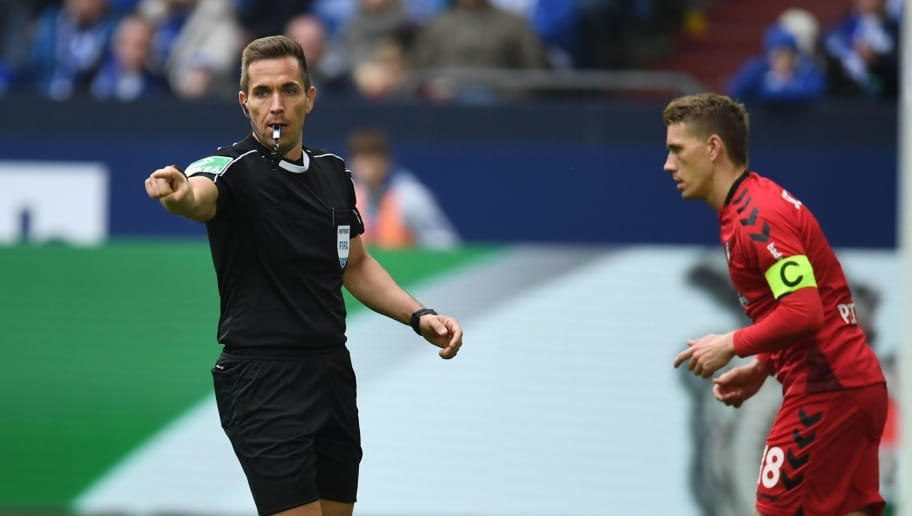 Referee Tobias Stieler reacts during the German first division Bundesliga football match FC Schalke 04 vs SC Freiburg, in Gelsenkirchen, western Germany, on March 31, 2018. / AFP PHOTO / Patrik STOLLARZ / RESTRICTIONS: DURING MATCH TIME: DFL RULES TO LIMIT THE ONLINE USAGE TO 15 PICTURES PER MATCH AND FORBID IMAGE SEQUENCES TO SIMULATE VIDEO. == RESTRICTED TO EDITORIAL USE == FOR FURTHER QUERIES PLEASE CONTACT DFL DIRECTLY AT + 49 69 650050         (Photo credit should read PATRIK STOLLARZ/AFP/Getty Images)